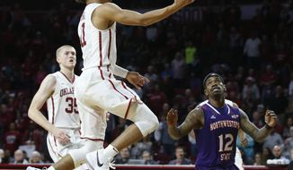 Oklahoma guard Trae Young, center, goes up for a shot in front of Northwestern State guard Jalan West (12) in the second half of an NCAA college basketball game in Norman, Okla., Tuesday, Dec. 19, 2017.  (AP Photo/Sue Ogrocki)