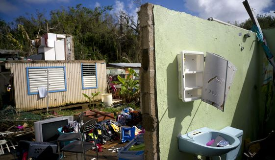 FILE - In this Oct. 14, 2017 file photo, what was once the home Arden Dragoni and his family lies in ruins after the passing of Hurricane Maria in Toa Baja, Puerto Rico. The Dragoni family lost everything on Sept. 20: clothes, household goods, and an old car, as well as the family's source of income: Arden Dragoni's construction work. (AP Photo/Ramon Espinosa, File)