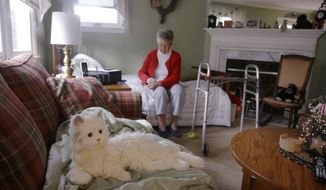 "In this Friday Dec. 1, 2017, photo, 93-year-old Mary Derr sits on her bed near her robot cat she calls ""Buddy"" in her home she shares with her daughter Jeanne Elliott in South Kingstown, R.I. Buddy is a Hasbro's ""Joy for All"" robotic cat, aimed at seniors and meant to act as a ""companion,"" it has been on the market for two years. Derr has mild dementia, and Elliott purchased a robot earlier this year to keep her mother company. (AP Photo/Stephan Savoia)"