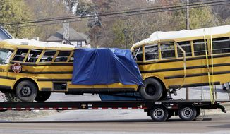 FILE - In this Nov. 22, 2016, file photo, a school bus is carried away on a trailer after a deadly crash in Chattanooga, Tenn. Prosecutors say Johnthony Walker, the driver in a Tennessee school bus crash that killed six elementary school students, took a cell phone call at the time of the crash. (AP Photo/Mark Humphrey, File)