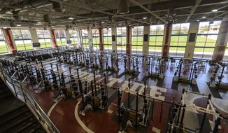 FILE - In this Feb. 27, 2013, file photo, the main room of Alabama's strength and conditioning facility is shown at the Mal Moore Athletic Facility at the University of Alabama in Tuscaloosa, Ala. Twenty-eight Power Five schools reported athletic revenue of more than $100 million, with Texas A&M leading the way at nearly $195 million. Each of the Power Five conferences made payouts to their members ranging between from $42 million in the Southeastern Conference to about $29 million in the Pac-12. (AP Photo/Alabama Media Group, Vasha Hunt) ** FILE **