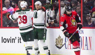 Minnesota Wild's Chris Stewart, center, and Nate Prosser celebrate a goal as Ottawa Senators' Erik Karlsson skates past during second period NHL hockey action in Ottawa on Tuesday, Dec. 19, 2017. (Sean Kilpatrick/The Canadian Press via AP)