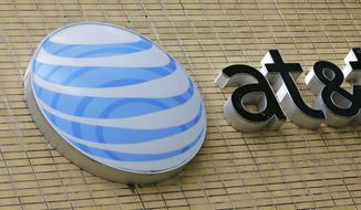 This Thursday, Oct. 12, 2017, file photo shows an AT&T sign at a store in Miami. On Dec. 20, 2017, the company announced it was giving employees a $1,000 bonus in celebration of congressional passage of federal tax reform. (AP Photo/Alan Diaz, File) **FILE**