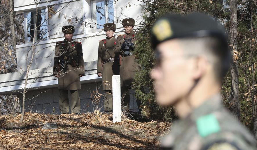 North Korean soldiers look at the South side as a South Korean stands guard near the spot where a North Korean soldier crossed the border on Nov. 13 at the Panmunjom, in the Demilitarized Zone, South Korea. South Korea says on Thursday, Dec. 21, 2017, it has fired 20 rounds of warning shots as North Korean soldiers approached a military demarcation line at the border after their comrade defected to South Korea. (AP Photo/Lee Jin-man, File)