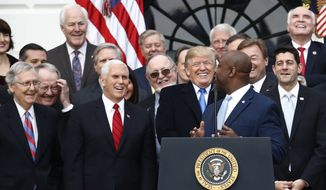 President Donald Trump smiles  with Senate Majority leader Mitch mcConnell of Ky., Vice President Mike Pence and House Speaker Paul Ryan of Wis., as Sen. Tim Scott, R-S.C., speaks during a bill passage event on the South Lawn of the White House in Washington, Wednesday, Dec. 20, 2017, to acknowledge the final passage of tax overhaul legislation by Congress. (AP Photo/Carolyn Kaster)