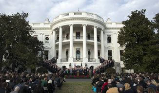 President Donald Trump surrounded by members of Congress and supporters as he speaks during an event on the South Lawn of the White House in Washington, Wednesday, Dec. 20, 2017, to acknowledge the final passage of tax overhaul legislation by Congress. (AP Photo/Carolyn Kaster)