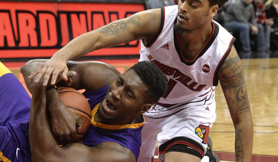 Louisville guard Quentin Snider (4) attempts to get the ball away from Albany forward Travis Charles (30) during the second half of an NCAA college basketball game, Wednesday, Dec. 20, 2017, in Louisville, Ky. Louisville won 70-68. (AP Photo/Timothy D. Easley)