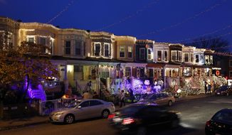 "In this Dec. 6, 2017, file photo, row houses in the Hampden neighborhood of Baltimore show off Christmas decorations.  Known as ""The Miracle on 34th Street,"" the dramatically over-the-top decor along the block is perhaps Baltimore's most beloved seasonal institution, attracting thousands of gawkers each December. (AP Photo/Patrick Semansky) ** FILE **"