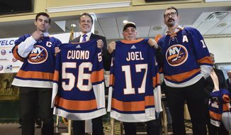 In this photo provided by the Office of New York Governor Andrew M. Cuomo, Gov. Cuomo, center left, poses with performer and Long Island native Billy Joel, center right, at a news conference at Belmont Park in Elmont, N.Y., Wednesday, Dec. 20, 2017. Cuomo announced on Wednesday that his 2018 budget contains funds to bring the New York Islanders NHL team back to Long Island to play in a new arena to be built on the grounds of Belmont Park. The Islanders left their original home at the Nassau Veteran's Memorial Coliseum and have played at the Barclays Center in Brooklyn, N.Y. since 2015. Joining Cuomo and Joel are New York Islanders captain John Taveres, left, and New York Islander Cal Clutterback, right. (Kevin P. Coughlin/Office of Governor Andrew M. Cuomo via AP)