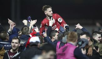Bristol City's Josh Brownhill celebrates their victory as he is lifted up by fans after the final whistle in the English League Cup Quarter Final soccer match between Bristol City and Manchester United at Ashton Gate, Bristol, England, Wednesday, Dec. 20, 2017. Bristol City defeated Manchester United 2-1. (Nick Potts/PA via AP)