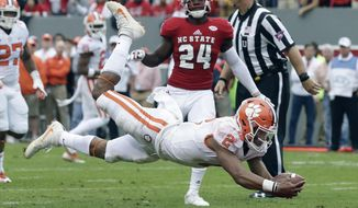 FILE - In this Nov. 4, 2017, file photo, Clemson quarterback Kelly Bryant (2) dives into the end zone for a touchdown while North Carolina State's Shawn Boone (24) looks on during the first half of an NCAA college football game, in Raleigh, N.C. Clemson will likely have a quarterback, two wide receivers and a running back starting their first playoff game at the Sugar Bowl against Alabama. But coach Dabo Swinney thinks Clemson's wins at Virginia Tech, Louisville and North Carolina State and a likely playoff elimination game in the ACC championship show the 2017 Tigers can handle the pressure. (AP Photo/Gerry Broome, File)