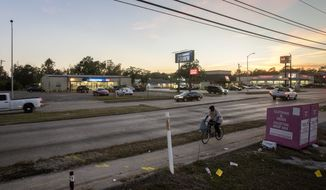 In this Friday, Dec. 1, 2017 photo, a man rides a bike past a pawn shop, located near the intersection of Homestead Road and Tidwell Road, in Houston. The pawn shop was looted during Hurricane Harvey, and dozens of firearms were stolen. (Jon Shapley/Houston Chronicle via AP)