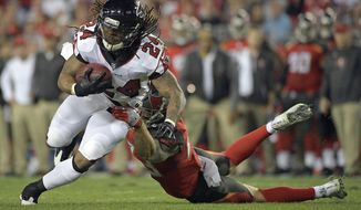 Atlanta Falcons running back Devonta Freeman (24) looks to get around Tampa Bay Buccaneers free safety Chris Conte, right, after a reception during the first half of an NFL football game, Monday, Dec. 18, 2017, in Tampa, Fla. (AP Photo/Phelan M. Ebenhack)