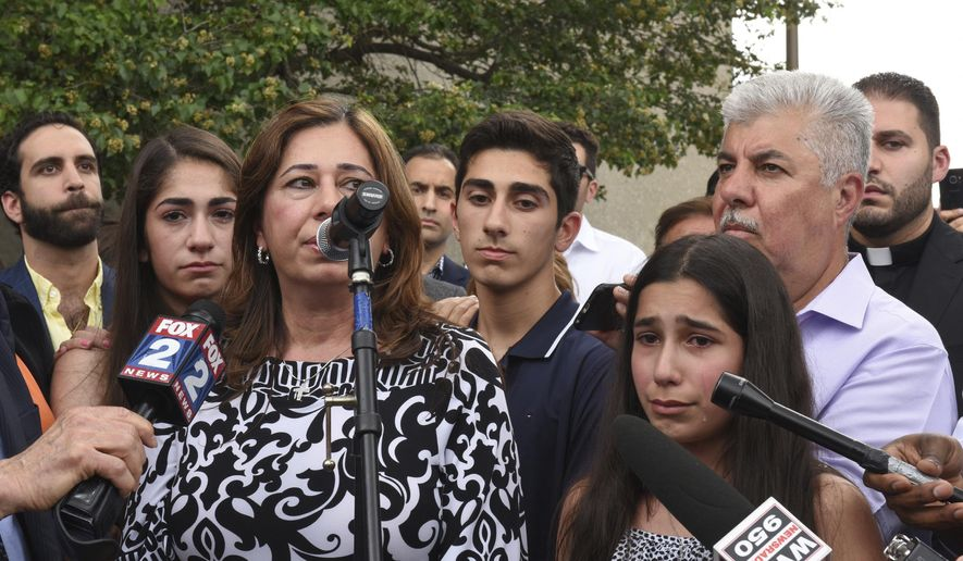 """FILE - In this June 16, 2017 file photo, Lindsey Hamama, 11, right, cries as her mother Nahrain speaks to the crowd in Detroit, about her father Usama """"Sam"""" Hamama, who was detained during Immigration and Customs Enforcement raids of primarily Chaldean immigrants, in which 114 Iraqi nationals in Metro Detroit were detained and are facing deportation. A federal judge in Detroit is mulling whether to release her father, Hamama, who was apprehended by immigration officials as part of a roundup in June, and hundreds of others whose deportations to Iraq were suspended but remain in custody. U.S. District Judge Mark Goldsmith, who will hear arguments on Wednesday, Dec. 20, 2017, blocked the deportation of 1,400 people in July to allow time to challenge their removal in immigration court. (Tanya Moutzalias/The Ann Arbor News-MLive.com Detroit via AP)"""