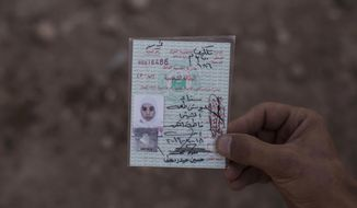 Fifteen-year-old Sana Younes died in a mortar attack in Mosul during the final battle to drive out Islamic State extremists, and her body was exhumed months later for forensic investigation. In this Oct. 9, 2017, photo, her brother Salem holds her identification card before her remains are reburied. (AP Photo/Bram Janssen)