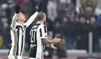 Juventus' Paulo Dybala, left, celebrates after scoring his team's first goal during an Italian Cup round of 16 soccer match between Juventus and Genoa, at Turin's Allians Stadium, Wednesday, Dec. 20, 2017. (Alessandro di Marco/ANSA via AP)