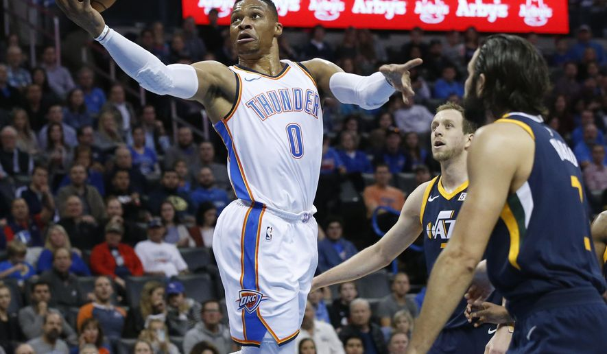 Oklahoma City Thunder guard Russell Westbrook (0) shoots in front of Utah Jazz forward Joe Ingles, center, and guard Ricky Rubio, right, during the first quarter of an NBA basketball game in Oklahoma City, Wednesday, Dec. 20, 2017. (AP Photo/Sue Ogrocki)