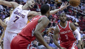 Los Angeles Lakers forward Larry Nance Jr. (7) reaches for a rebound between Houston Rockets forward Trevor Ariza (1) and guard Chris Paul (3) in the first half of an NBA basketball game, Wednesday, Dec. 20, 2017, in Houston. (AP Photo/Michael Wyke)