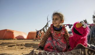 """In this Feb. 2017 photo Photo courtesy of Ryan Heffernan and Sesame Workshop, a young girl engages with Sesame Street caricature Elmo at an informal tented settlement near Mafraq,Jordan. The John D. and Catherine T. MacArthur Foundation announced Wednesday, Dec. 20, 2017, that Sesame Workshop and International Rescue Committee will get a $100 million grant from a Chicago-based foundation. for a joint program that will include home visits focused on early learning, child development centers and a local version of """"Sesame Street."""" (Ryan Heffernan/Sesame Workshop via AP)"""