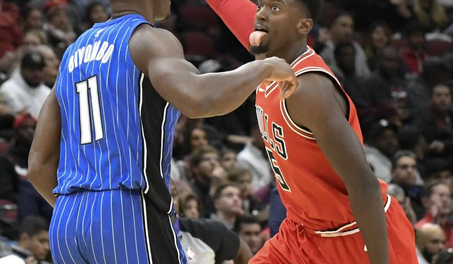 Chicago Bulls forward Bobby Portis (5) reacts after making a three-point basket as he runs past Orlando Magic center Bismack Biyombo (11) during the first half of an NBA basketball game, Wednesday, Dec. 20, 2017, in Chicago. (AP Photo/David Banks)