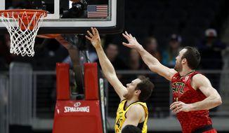 Indiana Pacers' Bojan Bogdanovic, left, of Croatia, puts up a shot past Atlanta Hawks' Miles Plumlee in the first quarter of an NBA basketball game in Atlanta, Wednesday, Dec. 20, 2017. (AP Photo/David Goldman)