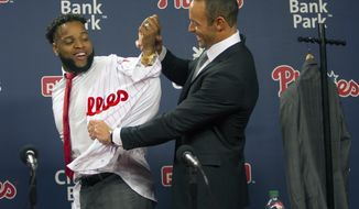Philadelphia Phillies manager Game Kapler, right, helps newly signed first baseman Carlos Santana put on his jersey as he was introduced to the media during a baseball press conference at Lincoln Financial Field in Philadelphia, Wednesday, Dec. 20, 2017. Jr(Jose F. Moreno/The Philadelphia Inquirer via AP)