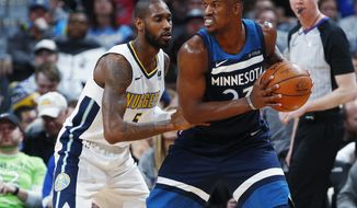 Minnesota Timberwolves guard Jimmy Butler, right, looks to pass the ball as Denver Nuggets guard Will Barton defends during the second half of an NBA basketball game Wednesday, Dec. 20, 2017, in Denver. The Timberwolves won 112-104. (AP Photo/David Zalubowski)