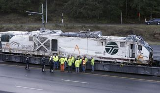 State Patrol officers and workers gather before transporting the engine from an Amtrak train crash two days earlier away from the scene, Wednesday, Dec. 20, 2017, in DuPont, Wash.  Federal investigators in the deadly train wreck want to know whether the engineer was distracted by a second person in his cab as his train hurtled into a curve at more than twice the speed limit.  The train took a 30 mph curve at 80 mph and plunged off an overpass, sending rail cars plummeting onto a busy highway south of Seattle.  (AP Photo/Elaine Thompson)