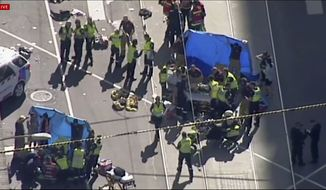 In this photo made video from the Australian Broadcasting Corp., emergency medical workers offer aid to victims struck by a vehicle, Thursday, Dec. 21, 20217, in Melbourne, Australia. Local media say over a dozen people have been injured after a car drove into pedestrians on a sidewalk in central Melbourne. (Australian Broadcast Corp. via AP)