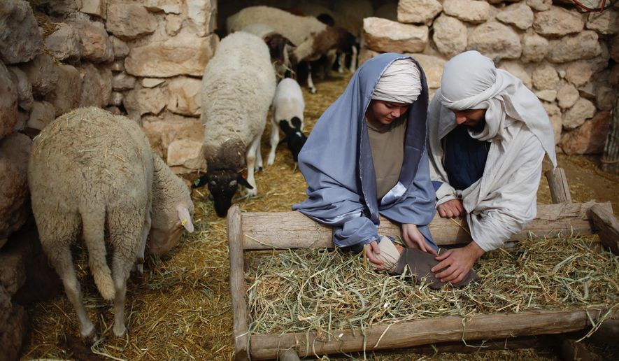 Christian actors portray Joseph and Mary during a re-enactment of a Nativity scene of the birth of Jesus Christ during Christmas festivities at the Nazareth Village in Nazareth, northern Israel , Thursday, Dec. 21, 2017. (AP Photo/Ariel Schalit)