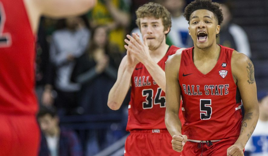 FILE - In this Dec. 5, 2017, file photo, Ball State's Ishmael El-Amin (5) and Sean Sellers (34) celebrate during the second half of an 80-77 win over Notre Dame in an NCAA college basketball game, in South Bend, Ind. This season was supposed to be different. Players talked openly about a third straight 20-win season, pursuing their first league title in 18 seasons, celebrating their first NCAA tourney win since 1990 and, yes, even adding a banner or two to the dusty collection. Everything changed for the Cardinals when 19-year-old 6-foot-9 forward Zach Hollywood was found dead in his apartment after committing suicide. Players wear a patch bearing Hollywood's initials just above their hearts. (AP Photo/Robert Franklin, File)
