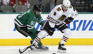 Dallas Stars center Tyler Seguin (91) and Chicago Blackhawks center Nick Schmaltz (8) compete for possession of the puck during the first period of an NHL hockey game in Dallas, Thursday, Dec. 21, 2017. (AP Photo/Michael Ainsworth)