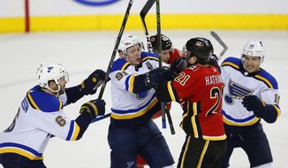 Calgary Flames' Garnet Hathaway (21) and St. Louis Blues' Vladimir Tarasenko (91) mix it up in front of Flames' Brett Kulak, rear, and Blues' Joel Edmundson (6) and Brayden Schenn (10) during the second period of an NHL hockey game Wednesday, Dec. 20, 2017, in Calgary, Alberta. (Todd Korol/The Canadian Press via AP)