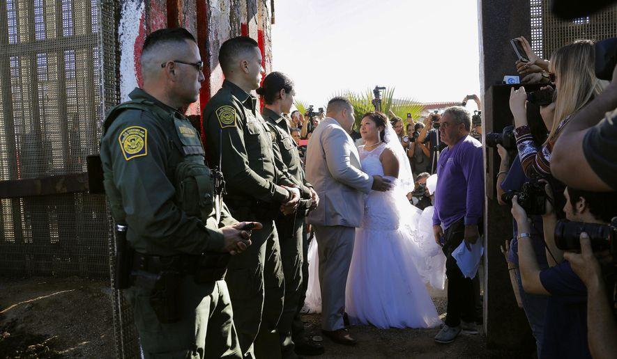 "In this Nov. 18, 2017, photo, Brian Houston, of Rancho San Diego, center left, and Evelia Reyes, right, of Tijuana, Mexico, look at each other in their wedding at the ""Door of Hope,"" part of the border fence between the U.S. and Mexico. A U.S. citizen, forbidden to enter Mexico, met and wed the love of his life in a brief moment when the gate separating the two countries was opened. Now it turns out the groom is a convicted drug smuggler and border agents are furious that he passed a federal background check and was approved for the ""Door of Hope."" (Howard Lipin//The San Diego Union-Tribune via AP)"