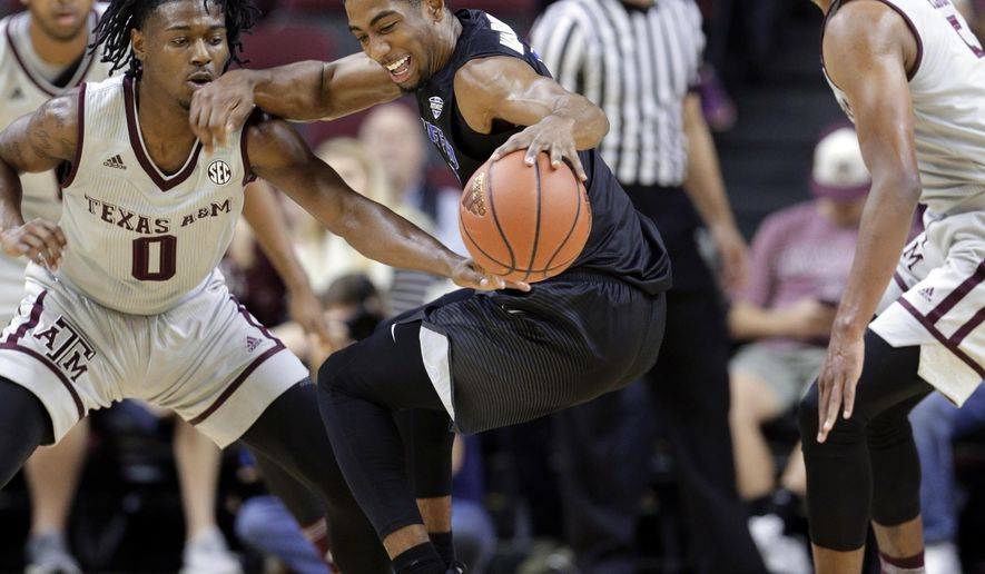 Texas A&M guard Jay Jay Chandler (0) knocks the ball away from Buffalo guard CJ Massinburg (5) as Texas A&M guard Savion Flagg (5) looks on during the first half of an NCAA college basketball game Thursday, Dec. 21, 2017, in College Station, Texas. (AP Photo/Michael Wyke)
