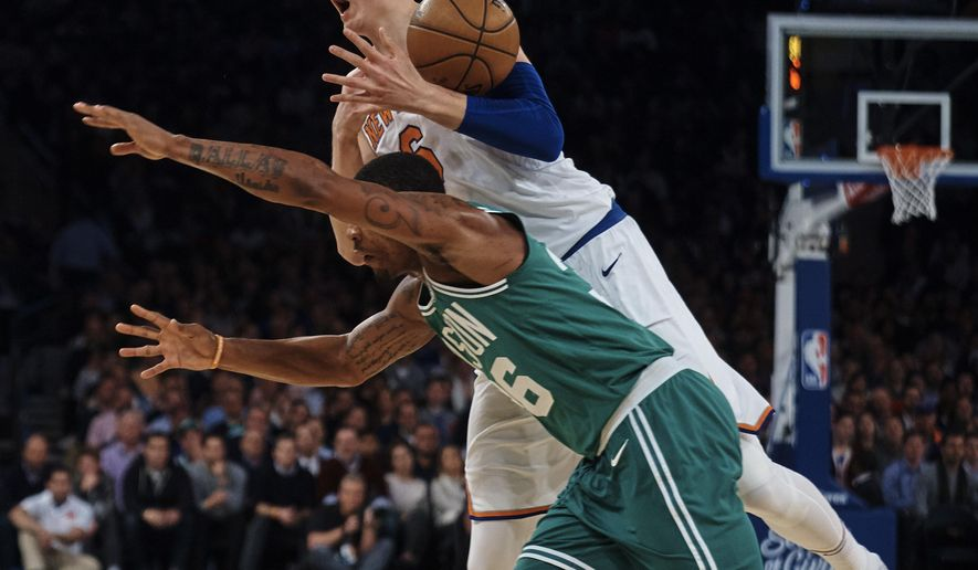 New York Knicks' Kristaps Porzingis, top, competes for the ball with Boston Celtics' Marcus Smart, bottom, during the first half of an NBA basketball game at Madison Square Garden in New York, Thursday, Dec. 21, 2017. (AP Photo/Andres Kudacki)