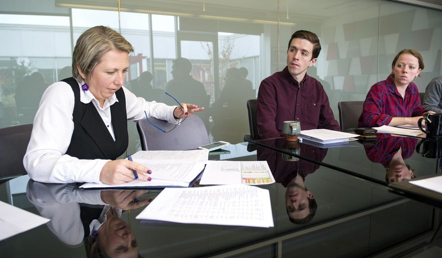 Dillon Moore, middle, and Katrina Steinley right, listens as Vera Krekanova Krofcheck, chief strategy officer for Partner4Work, discuss workforce strategy Tuesday Dec. 12, 2017, at the company's office in Pittsburgh, Pa. (Nate Guidry/Pittsburgh Post-Gazette via AP)