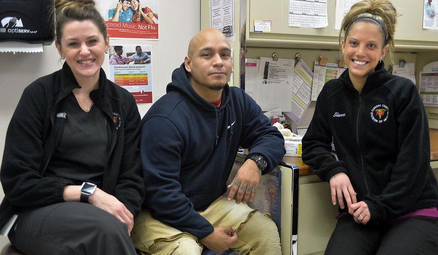 Labiano Valdez, center, sits with public health nurses Amanda Tuura, R.N., left, and Gianna Ventura, R.N., right, at the Kenosha County health department clinic in Kenosha, Wis., on Thursday, Dec. 7, 2017. Valdez is part of the county's Vivitrol program, which has helped him overcome his heroin addiction.   (Brian Passino/The Kenosha News via AP)
