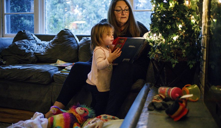 In this Nov. 30, 2017 photo, Carter Gens engages her grandmother Joanne Clough in one of her favorite activities - reading at their home in Camp Hill, Pa. Clough, 60,  is raising her granddaughter Carter since Carter's mother died of a fentanyl overdose last year. Clough's daughter Emily Roznowski, the mother of Carter, died on Dec. 3, 2016. (Dan Gleiter | dgleiter /PennLive.com via AP)