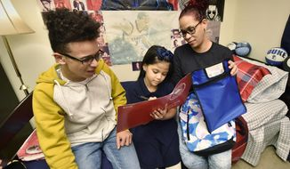 In this Wednesday, Dec. 6, 2017 photo, Madelyn Velez Santiago, right, looks over her 7-year-old daughter, Fabiola's, reading with her 15-year-old son, Luis, in the Lancaster Township, Pa., apartment where they are staying. Velez Santiago, who is from Mayaguez, Puerto Rico, now shares a modest apartment with her children and a childhood friend after Hurricane Maria devastated the island. (Blaine Shahan /LNP via AP)