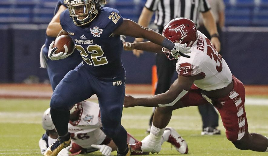 FIU running back Shawndarrius Phillips (22) carries as Temple linebacker William Kwenkeu (35) reaches for him during the Gasparilla Bowl NCAA college football game Thursday, Dec. 21, 2017, in St. Petersburg, Fla. (Al Diaz/Miami Herald via AP)