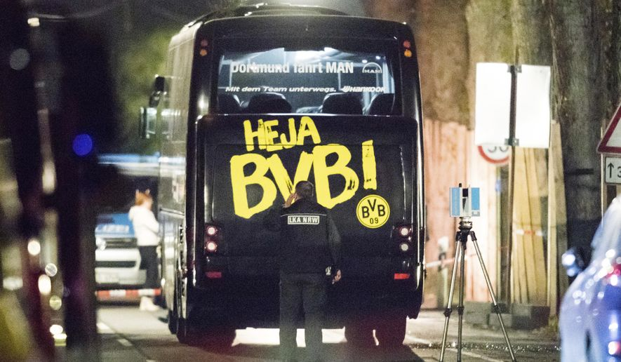 FILE - In this April 12, 2017 file photo a police officer investigate the crime scene after Borussia Dortmund's team bus was hit by an explosion on their way to the Champions League match against Monaco in Dortmund, western Germany. On Thursday, Dec. 21, 2017 a man will go on trial. He is charged with the attempted murder of Borussia's soccer team by detonating homemade bombs when traveling to the match. (Marcel Kusch/dpa via AP)