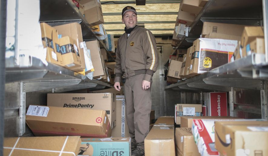 In this Monday, Dec. 18, 2017 photo, Branden Holverson poses for a photo inside a UPS truck in Idaho Falls, Idaho. Holverson, who has worked for UPS for 10 years, is on schedule to deliver close to 300 packages on Monday but has had a peak of close to 500 closer to Christmas. (John Roark/The Idaho Post-Register via AP)