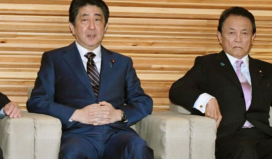 Japanese Prime Minister Shinzo Abe, left, sits with Finance Minister Taro Aso, right, for a Cabinet meeting at his official residence in Tokyo Friday, Dec. 22, 2017. Abe's Cabinet approved Japan's biggest 5.19 trillion yen ($46 billion) defense budget on Friday to bolster ballistic missile defense capability amid escalating threats from North Korea. (Hitoshi Takano/Kyodo News via AP)