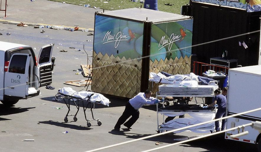 FILE - In this Oct. 2, 2017 file photo, investigators load bodies from the scene of a mass shooting at the Route 91 Harvest festival near the Mandalay Bay resort and casino on the Las Vegas Strip on in Las Vegas. A coroner in Las Vegas says all 58 victims in the Oct. 1 mass shooting on the Las Vegas Strip died of gunshot wounds. Clark County Coroner John Fudenberg told The Associated Press on Thursday, Dec. 21, that all the cases were ruled homicides. (AP Photo/Chris Carlson, File)
