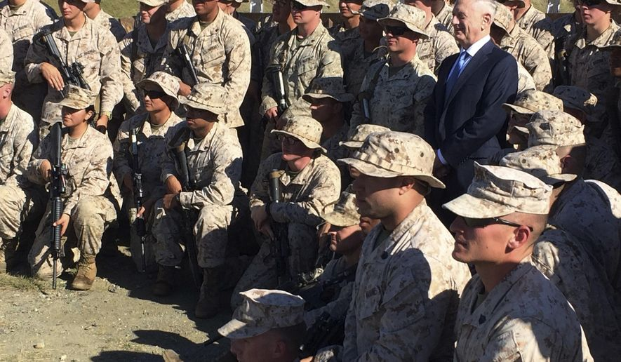 Defense Secretary Jim Mattis poses for a photo with U.S. Marine Corps troops at a rifle range at Guantanamo Bay, Cuba, on Thursday, Dec. 21. 2017. The unannounced visit was the first by a defense secretary since Donald Rumsfeld visited in January 2002 shortly after the first prisoners arrived from Afghanistan. (AP Photo/Robert Burns)