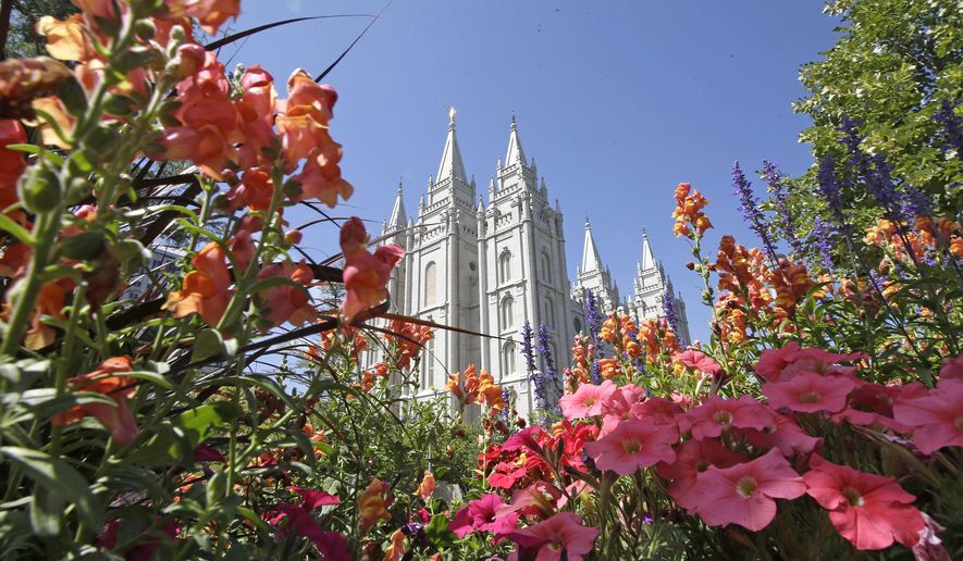 This Aug. 4, 2015, file photo, flowers bloom in front of the Salt Lake Temple, at Temple Square, in Salt Lake City. (AP Photo/Rick Bowmer, File)