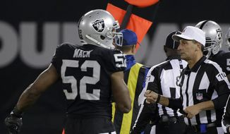 FILE - In this Sunday, Dec. 17, 2017, file photo, referee Gene Steratore (114) carries a folded piece of paper used to determine a measurement next to Oakland Raiders defensive end Khalil Mack (52) during the second half of an NFL football game between the Raiders and the Dallas Cowboys in Oakland, Calif. The NFL on Thursday, Dec. 21, 2017, has told its officials not to use index cards or any other paper to aid in measurements. (AP Photo/Eric Risberg, File)
