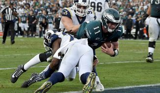 FILE - In this Sunday, Dec. 10, 2017 file photo, Philadelphia Eagles quarterback Carson Wentz gets tackles during the second half of an NFL football game against the Los Angeles Rams in Los Angeles. Wentz left the game shortly after the play and did not return to the game. From Carson Wentz to Deshaun Watson to Marcus Mariota and Jameis Winston, injuries take their tolls on young NFL quarterbacks. (AP Photo/Mark J. Terrill, File)
