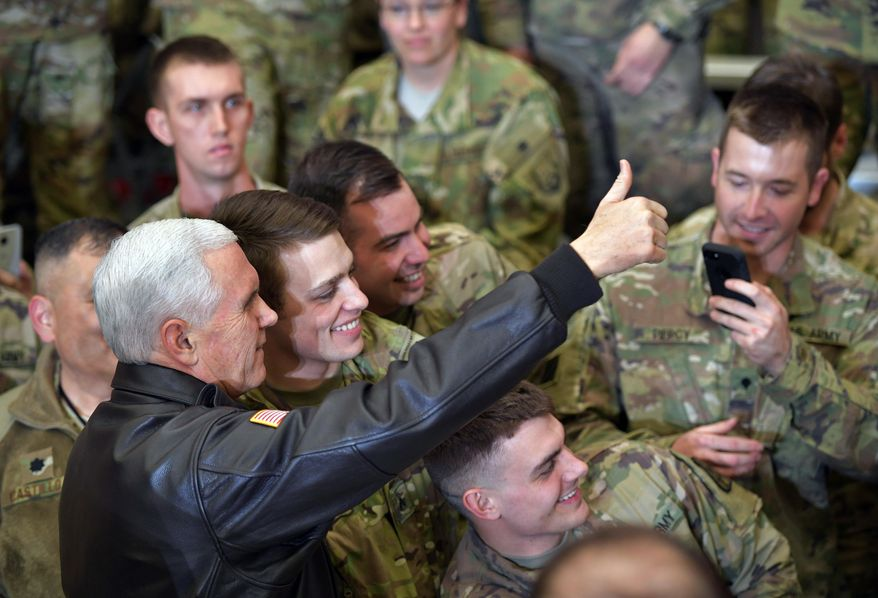 U.S. Vice President Mike Pence poses for photos with troops at Bagram Air Base in Afghanistan on Thursday, Dec. 21, 2017. (Mandel Ngan/Pool via AP)